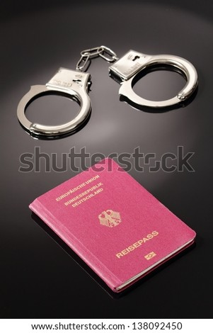 Passport with handcuffs - stock photo