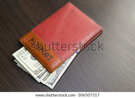Passport with money lying on a wooden table