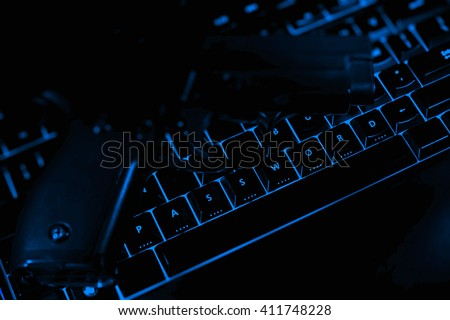 Password text and pistol on the illuminated buttons of the keyboard by night. Internet safety concept.  - stock photo