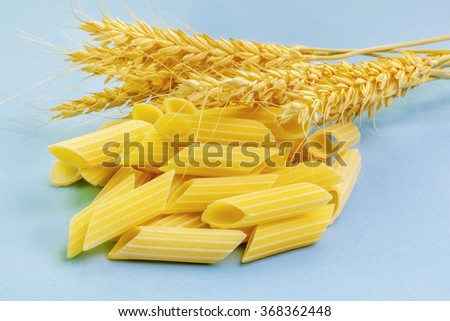 Pasta and ears of wheat on light blue