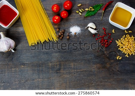 Pasta and ingredients on dark wooden background with copy space. Top view. Vegetarian food, health or cooking concept. - stock photo