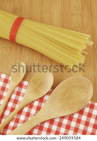 Pasta and spoons on wooden background with tablecloth
