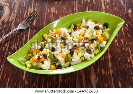 Pasta and vegetable salad on a rustic wood table - stock photo