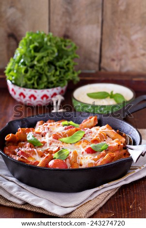 Pasta bake with whole wheat penne, tomatoes and mozarella - stock photo