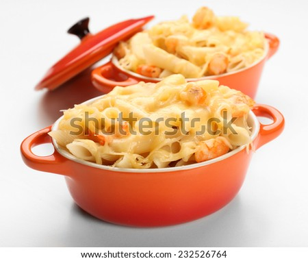 Pasta baked with shrimps and cheese in ceramic pot, isolated on white - stock photo