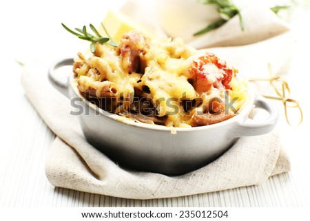 Pasta baked with vegetables and cheese in ceramic pot - stock photo