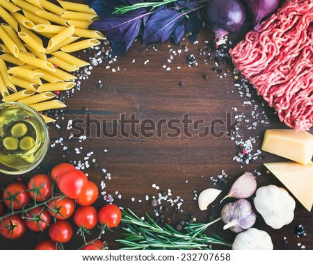 Pasta Bolognese ingredients: penne, minced meat, tomatoes, basil, rosemary, parmesan cheese, olive oil, garlic, onion, sea salt and spices on a dark stone background with a copy space in the center - stock photo