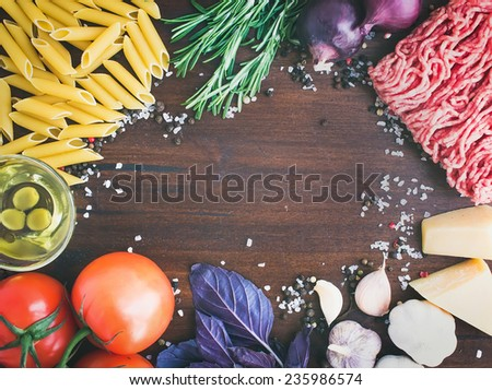 Pasta Bolognese ingredients: penne, minced meat, tomatoes, basil, rosemary, parmesan cheese, olive oil, garlic, onion, sea salt and spices on a dark wooden background with a copy space in the center - stock photo