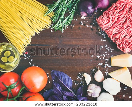 Pasta Bolognese ingredients: spaghetti, minced meat, tomatoes, basil, rosemary, parmesan cheese, olive oil, garlic, onion, sea salt and spices on a dark wood background with a copy space in the center - stock photo