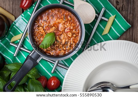 Pasta, bolognese sauce and basil on wooden table. Top view.