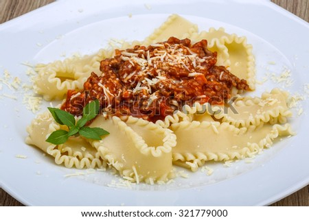 Pasta Bolognese with parmesan cheese and basil leaves