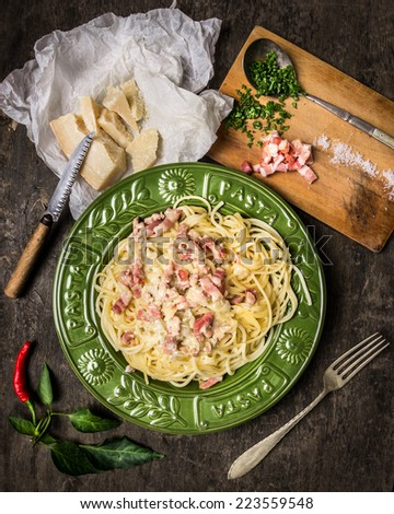 Pasta Carbonara in  green plate , parmesan, spices and seasonings on dark wooden background  - stock photo