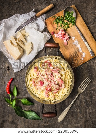 pasta carbonara in vintagen pan with parmesan cheese ,spices and herbs on cutting board, top view - stock photo