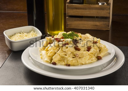 pasta carbonara served on penne with bacon, parsley and sweet sour cream white sauce.