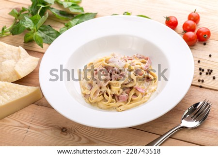 Pasta carbonara with bacon on wooden background - stock photo