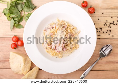 Pasta carbonara with bacon on wooden background. Top view - stock photo