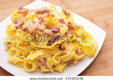 pasta Carbonara with eggs bacon and parmesan on wooden board - stock photo