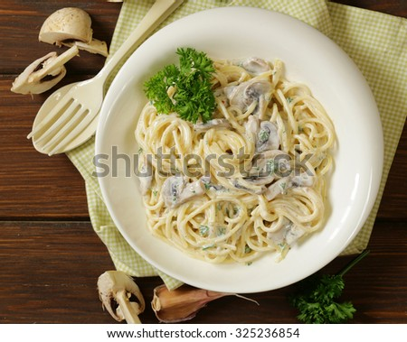 pasta carbonara with mushrooms, garlic and parsley - stock photo