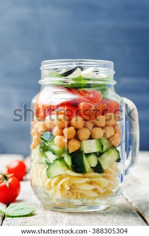 Pasta chickpeas cucumber tomatoes spinach goat cheese salad in a jar. toning. selective focus - stock photo