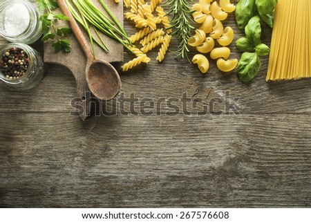Pasta collection with herbs and spices on rustic wooden background - stock photo