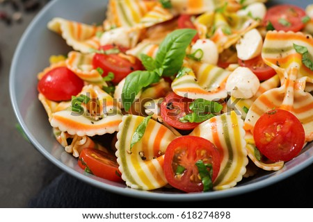 Pasta colored farfalle salad with tomatoes, mozzarella and basil.