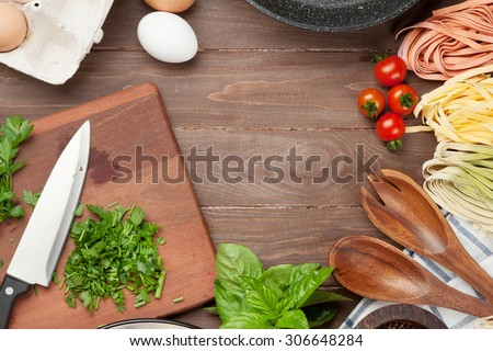 Pasta cooking ingredients and utensils on wooden table. Top view with copy space - stock photo