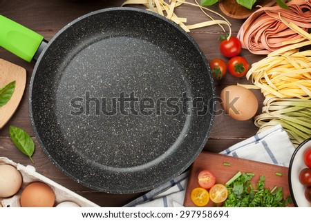 Pasta cooking ingredients and utensils on wooden table. Top view with empty frying pan for copy space - stock photo