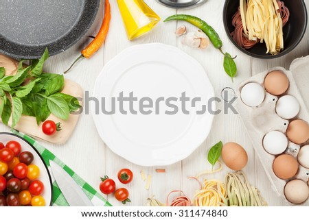 Pasta cooking ingredients and utensils on wooden table. Top view with empty plate for copy space - stock photo