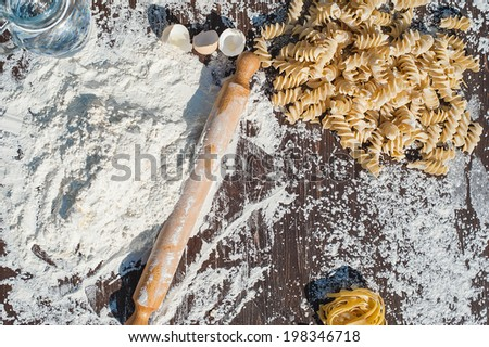 Pasta egg in flour and a rolling pin. - stock photo