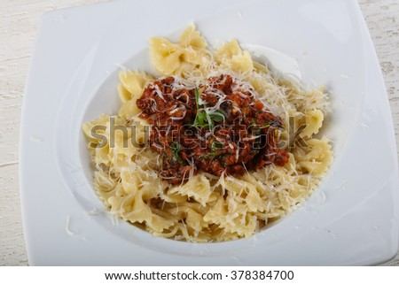 Pasta farfalle bolognese with parmesan cheese and thyme
