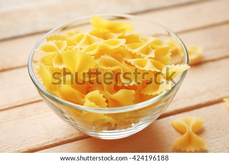 Pasta farfalle in bowl on wooden table background