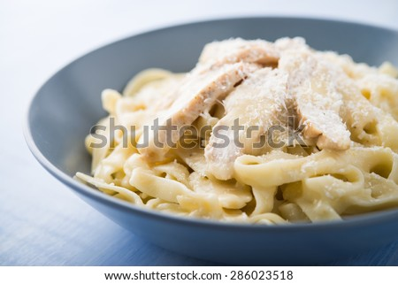 Pasta fettuccine alfredo with chicken and parmesan on blue wooden background close up. Italian cuisine. - stock photo