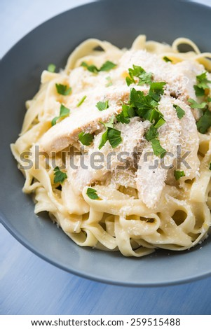 Pasta fettuccine alfredo with chicken, parmesan and parsley on blue wood background close up. Italian cuisine. - stock photo