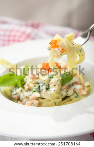 Pasta fettuccine with seafood on kitchen table - stock photo