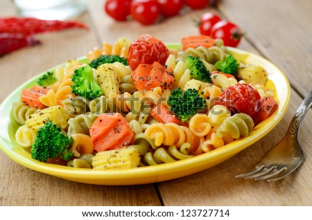 Pasta fusilli salad with broccoli, carrot, corn and tomatoes on the kitchen table - stock photo