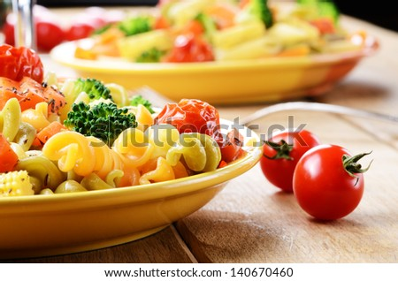 Pasta fusilli salad with broccoli, carrot, corn, and tomatoes on the kitchen table - stock photo
