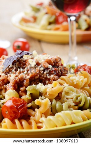 Pasta fusilli with bolognese sauce and dried tomatoes on the kitchen table