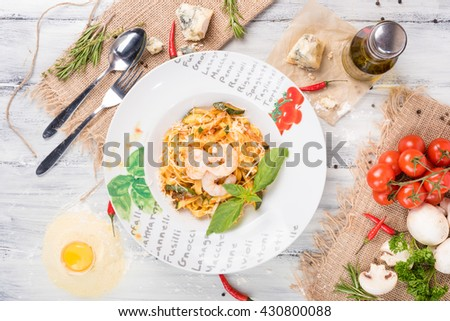 pasta in a tomato sauce with shrimp on a plate on the table. horizontal view from above
