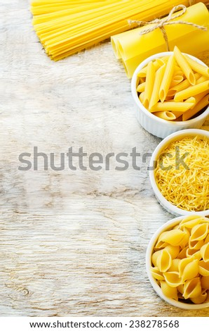 pasta in a white bowl on white wood background. tinting. selective focus - stock photo