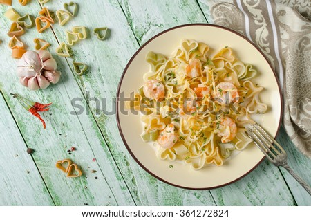 Pasta in cream sauce with shrimp. Cooking with love - stock photo
