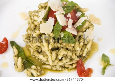 Pasta in white garlic sauce with cherry tomatoes, parmesan cheese and basil leaves