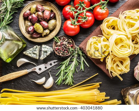 Pasta ingredients. Cherry-tomatoes, spaghetti pasta, rosemary and spices on a graphite board. - stock photo