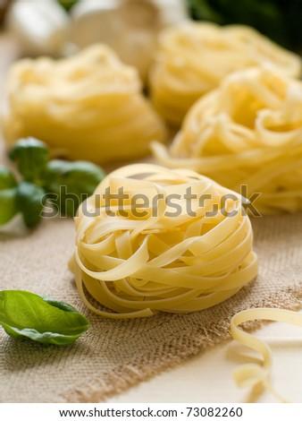 Pasta ingredients; fresh tagliatelle, garlic,basil  Selective focus - stock photo