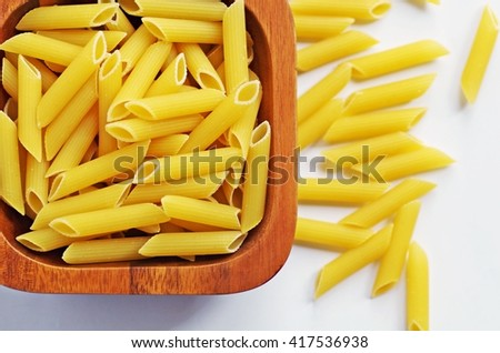 Pasta. Italian pasta. Raw penne pasta. Penne pasta. Raw pasta in wooden bowl on white background. Italian penne rigate macaroni pasta. Macaroni pasta. - stock photo