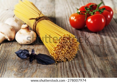 Pasta. Italian spaghetti with mushrooms, basil and and cherry tomatoes on the wooden table. Products for cooking dish of spaghetti  - stock photo