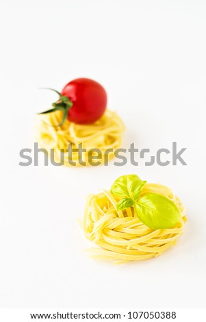 Pasta nests with cherry tomatoes and basil on white background