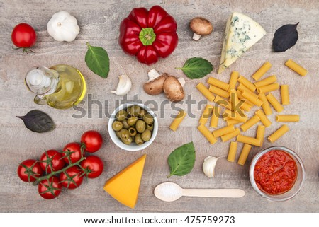 Pasta, oil, vegetables and sauce â?? healthy food ingredients on a wood table background