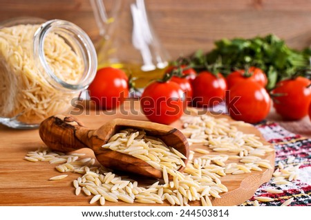 Pasta Orzo in the form of rice grains in a wooden scoop - stock photo