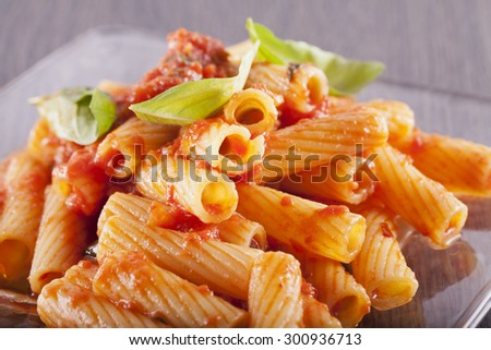 Pasta over glass plate, with tomato and basil, horizontal image