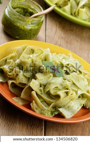 Pasta papardelle with pesto sauce and basil closeup shot